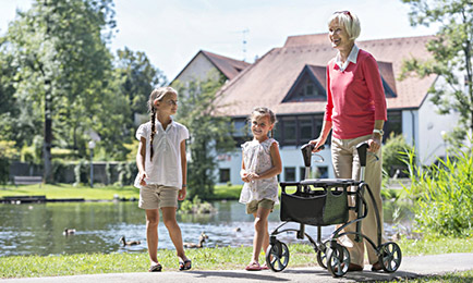 grandmother with 2 young girls walking with her walker, this describes our blog post about aging